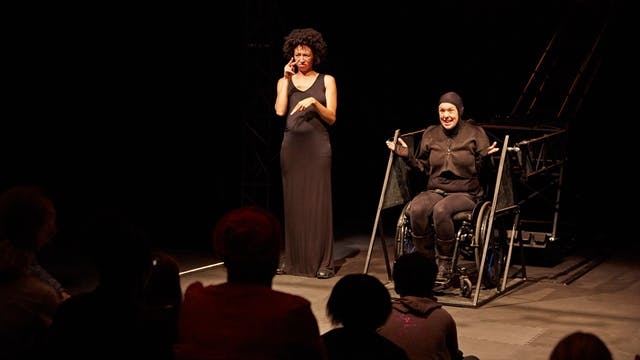 Jess Thom performing on a stage with a BSL interpreter, Charmaine Wombwell. The backdrop is black. Jess and Charmaine are both wearing black and are in front of an audience.