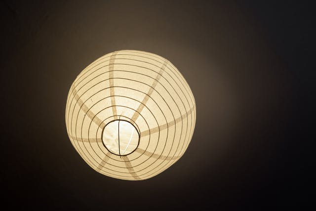 Photograph looking up at a spherical paper ceiling lampshade. The lamp is on, illuminating the lampshade and a patch of the ceiling. The lampshade is made of paper and a spiralling metal wire. The image has a warm tone to it.
