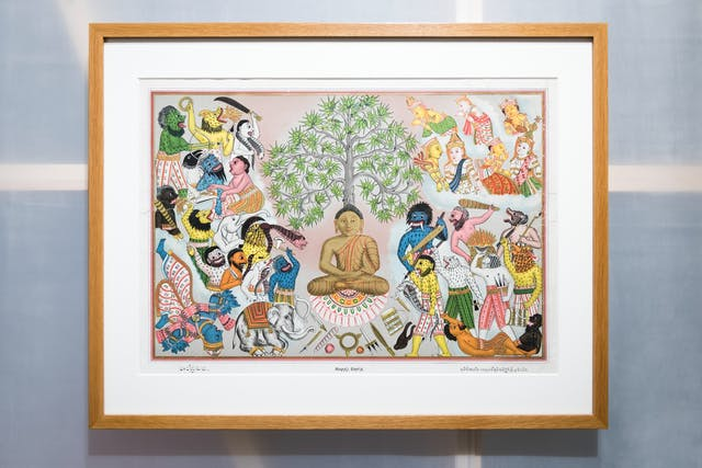 画廊中的一张照片显示了半透明墙的一部分,展示了后面的木结构,木框中挂着一幅相框版画。在画框内的一个窗台上,有一幅色彩鲜艳的图画,画的是一位佛陀在抗拒试图阻止他悟道的魔罗,而天使则在上面看着他。