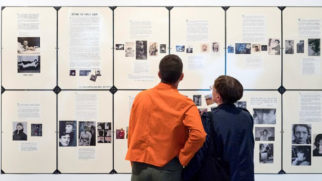 Photograph of two people in the Misbehaving Bodies Exhibition. They have their backs to the camera looking at a display on the wall.
