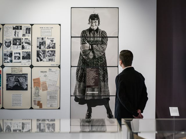 Photograph of a man in a dark jacket looking at a life-size picture of Jo Spence in the Misbehaving Bodies Exhibition at the Wellcome Collection.  The man has his back to us whilst the picture of Jo Spence is gazing straight at the viewer of the picture. To the left of the photograph are various tear sheets from the work fo Jo Spence that make up