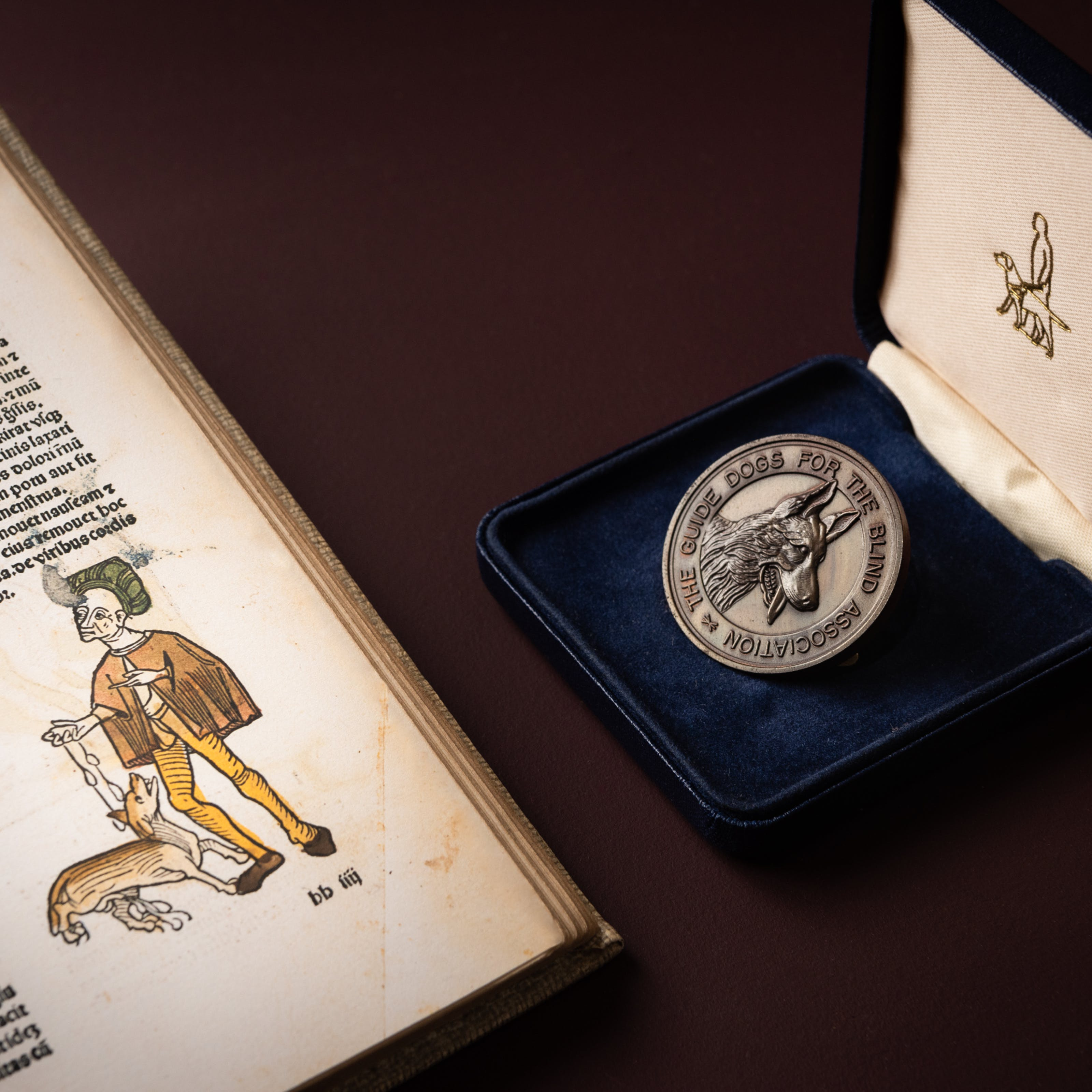 A photograph showing part of a medieval book on the left had-side of the image featuring Latin text and a figure of a man wearing a cape, tunic and a feathered hat. He is holding a dog on a lead, and the illustration is coloured green, brown and yellow.  On the right-hand side of the image is a medallion with The Guide Dogs For The Blind Association engraved around the outside, and an alsation dog's head engraved in the middle. The medallion is sitting in a royal blue box lined with blue velvet. The inside of the lid is lined with a cream coloured material on which the black outline of a guide dog and guide dog handler is stitched. The items appear on a plain brown background.
