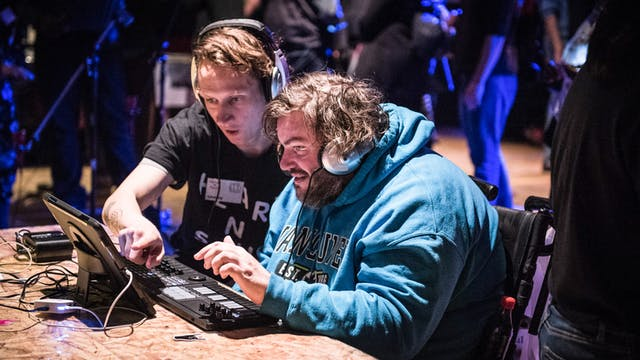 Photograph of two men sitting together at a table, wearing headphones and using a music mixing desk.