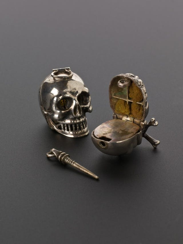 Image of a small silver vinegar container in the shape of a skull.