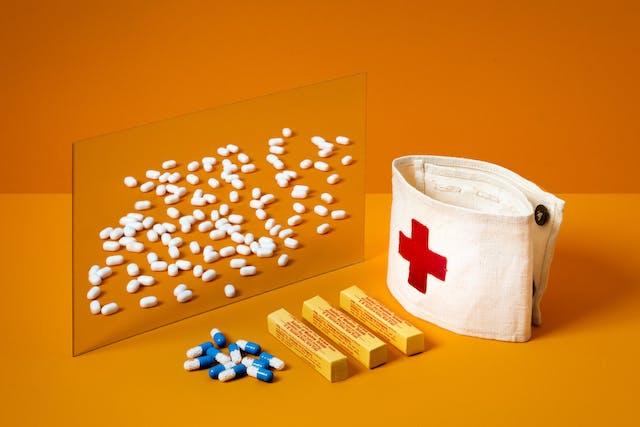 橙色背景下镜子的照片。在前景是一个医生的袖章与红十字会,包的止痛药和一些松散的药丸。镜子里映照着几十颗白糖丸。
