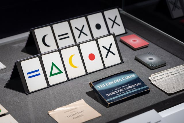 Photograph of a set of telepathy cards which have symbols printed on them, as part of the Smoke and Mirrors exhibition at Wellcome Collection.