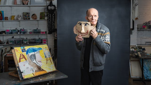Photograph of stroke survivor and artist Chris Miller in an artist studio. A grey textured background frames the artist as he holds a ceramic of a head, which acts as a cartoon likeness of his own face. Miller's gaze is directed towards the viewer.  In the background of the studio the room is layered with artworks. To the left of the frame is a yellow painting on a table top easel.