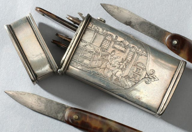 Photo of an engraved metal container with several blades inside and two blades either side of it.