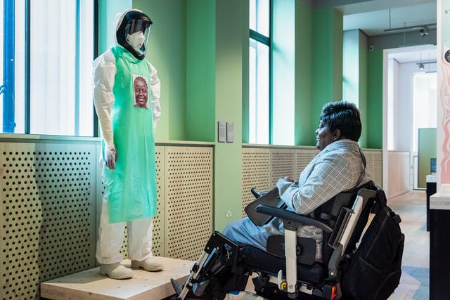 A photograph showing a visitor seated in a wheelchair looking at a model wearing a white hazmat suit, visor and green apron standing on a low wooden platform. On the green apron there is a stickered portrait of the carer that would have been wearing the suit whilst treating Ebola patients.