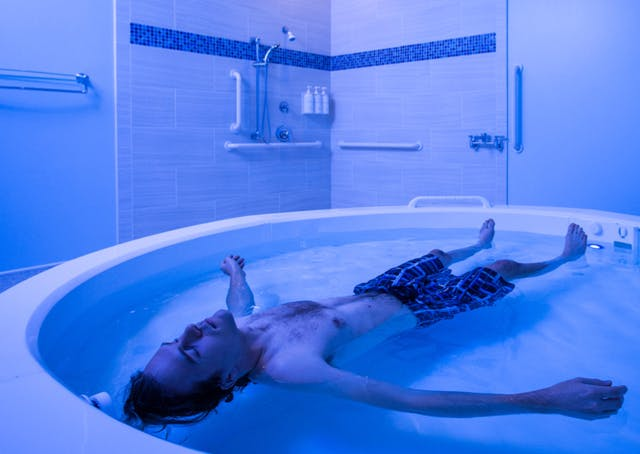 A man lies in a blue-lit pool of water.