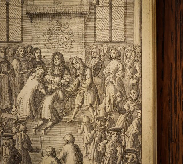 A photograph of an open book against a dark wood background. The page of the book shows an illustration depicting a crowded official ceremony with the King presented with diseased men who are kneeling in front of him.