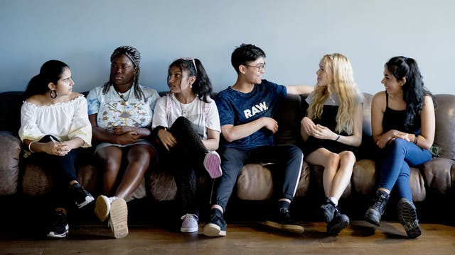Six young people from the RawMinds Ambassadors sit on a sofa, talking to each other.