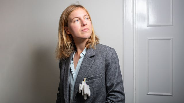 Portrait of Dr Camilla Mørk Røstvikis with tampons hanging out of the breast pocket of her blazer.