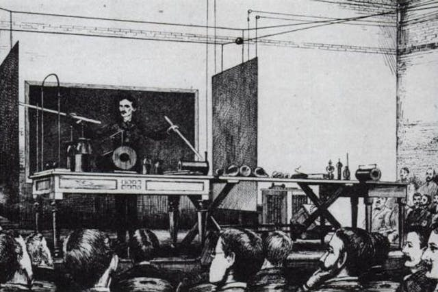 Illustration of Nikola Tesla at the front of a room demonstrating to crowds by pointing at equipment using sticks.