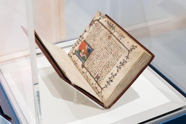 照片的一个展览玻璃展示柜显示一个开放的手稿,在一个书摇篮。打开的双页展页显示了复杂的文字和页图画的装饰,在文本的开始彩色的照明。