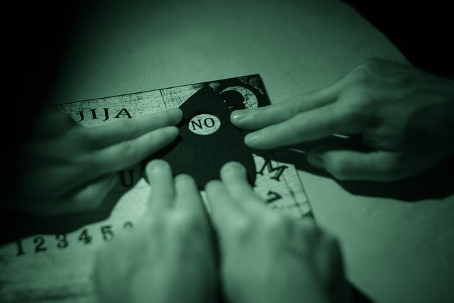 Photograph of a ouija board with the hands of three people resting on the planchette. The image is toned green as a result of being made under infrared light.