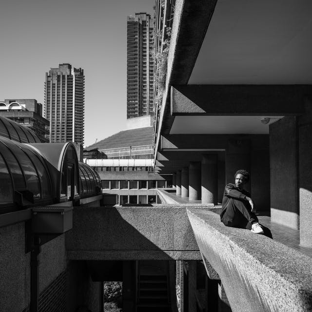 Photograph in black and white of a man sitting on a walkway balcony looking out at the Barbican Centre, London.