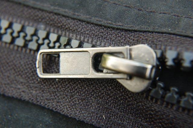 Photograph of a black zipper holding together black denim fabric, halfway unzipped.