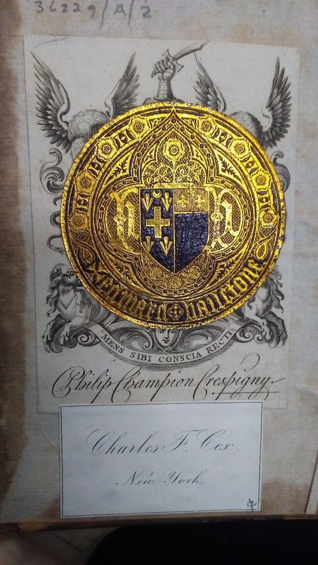 Three bookplates overlaying each other.  A circular gilt leather bookplate with a coat of arms in the centre and the name Edward Hailstone overlays a rectangular monochrome printed bookplate which bears what appears to be another coat of arms and the name Philip Champion Crespigny.  Below this is a smaller, more recent bookmark with the words