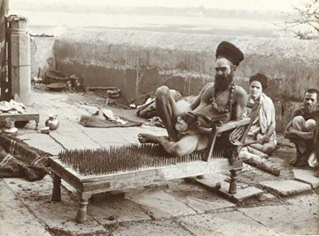 A fakir or yogi sitting on a bed fo nails