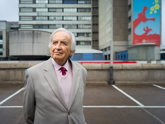Photographic portrait of Morgan David Enoch standing in front of University Hospital of Wales.
