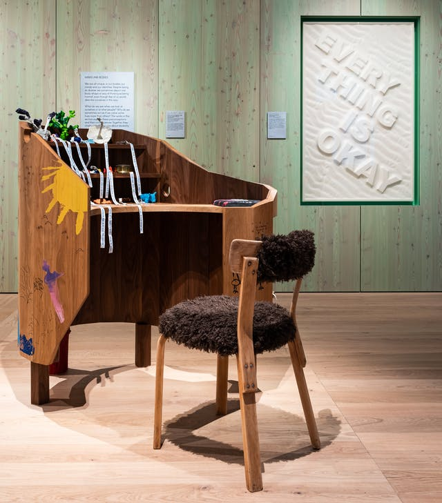 Photograph of two artworks in a gallery space. In the foreground is a desk-like piece of furniture with a desk chair covered in a fur-like material. In the background, recessed into the wall, is an artwork with the words