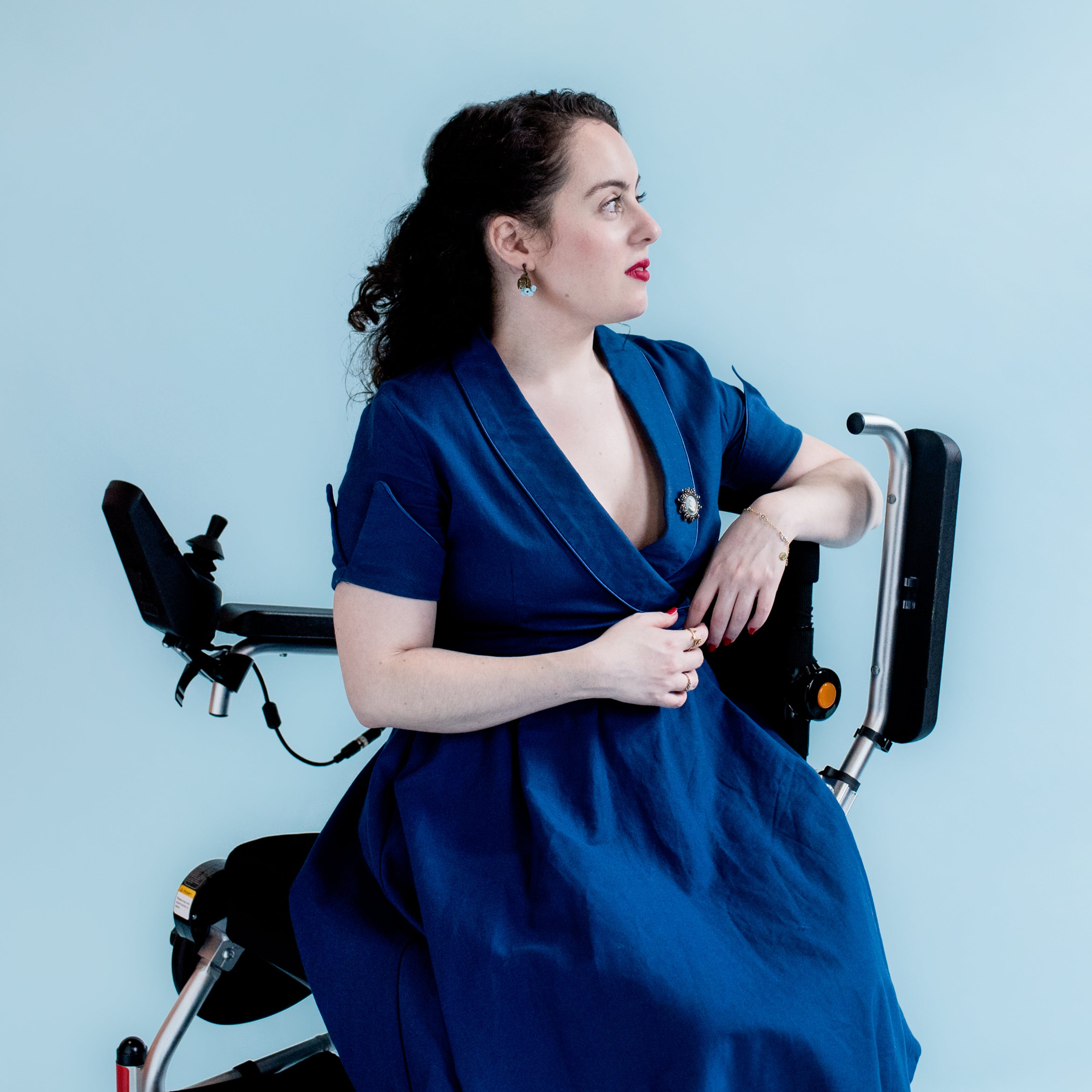 Photograph of a young woman in a blue dress with a broach sitting side-on in her wheelchair against a light blue background. She is looking off to the right of camera, face in profile.