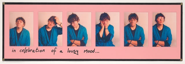 "Photograph of a pink sheet of paper with 6 colour photographs mounted on top in a row. Each images shows a woman in a blue dressing gown pulling a different pose. Sometimes arms folded, one with her head in hands, another scratching her head. Under the row of photographs are the handwritten words, ""in celebration of a lousy day"". The whole collage is laminated."