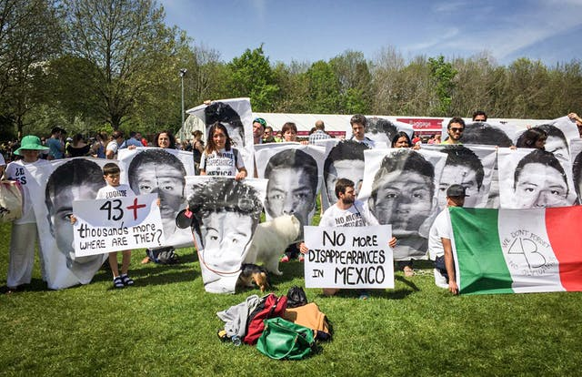 Photograph of a young woman standing in a park, in a sea of protest banners, bearing the faces of people who have disappeared in mexico.