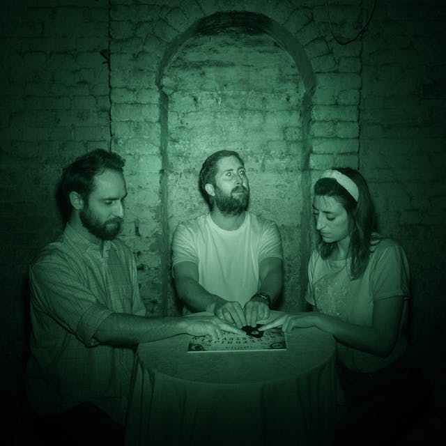 Photograph of three people sat at a round table in a cellar. Behind them is a white brick wall with an arch. Their hands rest on the planchette of a ouija board. The image is toned green as a result of being made under infrared light.