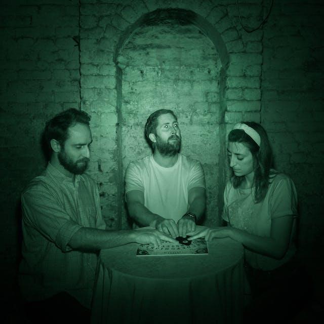 三个人坐在地下室的圆桌旁的照片。他们身后是带拱门的白砖墙。他们的手放在显灵板的占卜板上。由于是在红外光下拍摄的,这幅图像呈绿色。