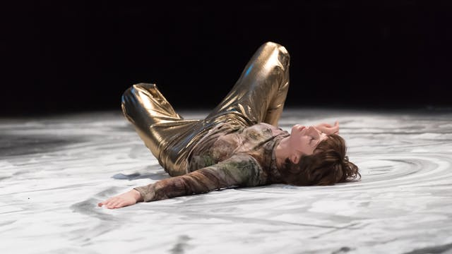Photograph of a dancer lying on a salt-covered floor. They are wearing gold trouser and a patterned top with muted colours. Their eyes are shut and the dance has made patterns in the salt on the floor.