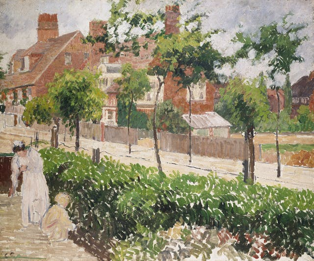 Painting by Camille Pissarro in the Impressionist style of small but visible brush strokes. Shows a road with red-brick houses in the background and leafy green shrubs and taller trees. A women and child dressed in white and beige tend to the greenery in the foreground.