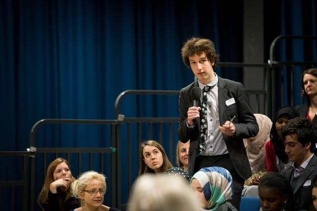 Photograph of a young man talking into a microphone at an event.