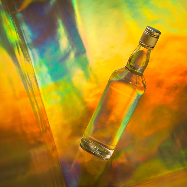 Photograph of an alcoholic spirit bottle on a colourful background.