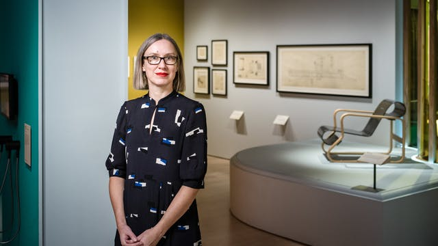 Photograph of Emily Sargent, curator of the exhibition Living with Buildings, standing in the gallery space.