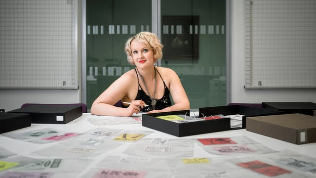 Photographic portrait of Dr Kate Lister sat at a table with a selection of archive material from the sex worker card collection at Wellcome Library laid out infront of her.
