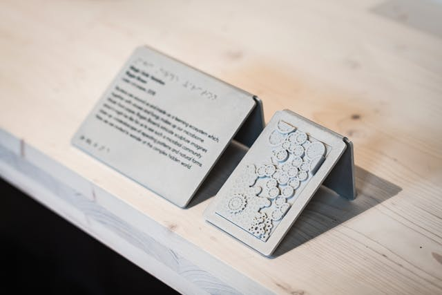 A photograph of a caption, black text shown as out of focus and displayed on a small silver display plaque positioned at 45 degrees to wooden surface, alongside a similar sized touch tile to allow visitors to feel a texture or shape of an exhibit without touching the object itself. The touch tile shows what looks like a series of cogs shown in relief.