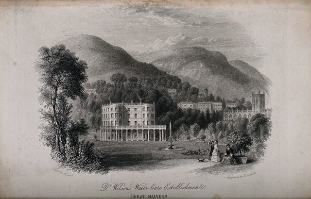 Black and white etching showing people in long-skirted outfits walking in the grounds beside a large white building with trees and hilly countryside behind.