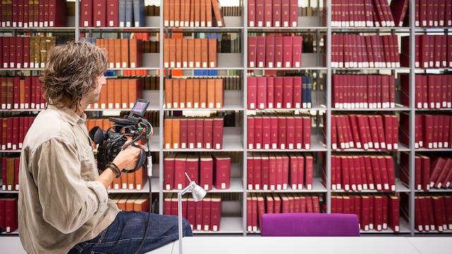 图书馆书架上堆满了书,书脊朝外。所有的刺都是红色、橙色或绿色的。在前景中,一个男人坐在一个长长的白色桌面上,手里拿着一个大型的专业胶片相机,带有一个小屏幕和突出的电线。他朝书架望去。