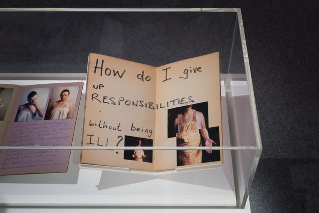 Photograph of a section of a gallery display case showing the open pages a scrapbook. The open page shows three photographs of a woman wearing a yellow pattered apron, with her hands outstretched. On the page is written the words,