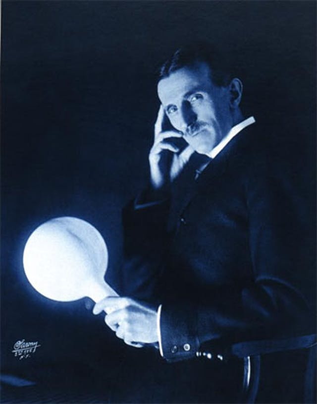 Black and white photograph of Nikola Tesla sitting with one hand on his face and the other grasping a bulb that is glowing with light.