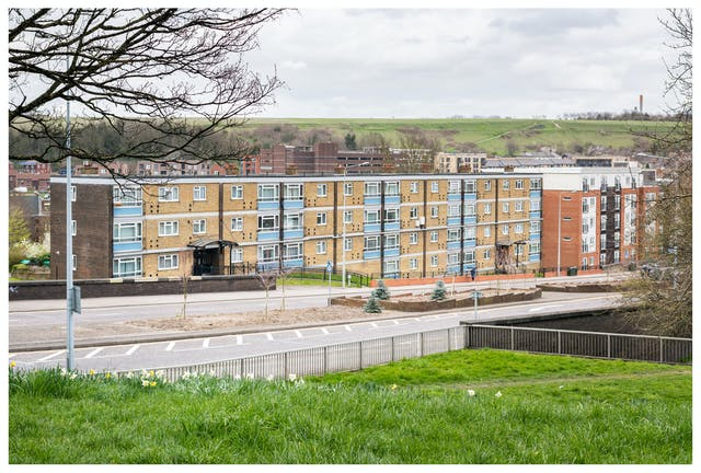Photograph of modern blacks of flats next to a dual carriageway. The buildings and the road run across the middle of the image. In the background there are hills of green fields and trees. In the foreground and across the bottom of the image there is a grass verge overlooking the road with yellow and white daffodils.