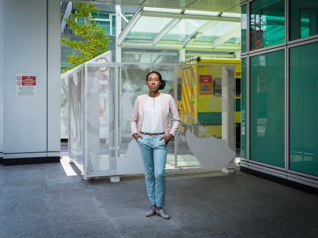 Photographic full length portrait of Sarah Itam, urological surgeon, outside University College London Hospital.