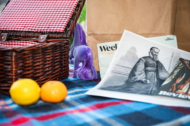 Photograph of a checkered picnic blanket, fairly closeup. On the left is an open wicker picnic hamper, in front of which is a lemon and a clementine. To the right of the image is a collection of newspaper supplements within which is a black and white print of a bearded man wearing long robes and a ruff. In the centre of the image is the rear end of a purple unicorn disappearing behind the picnic hamper.