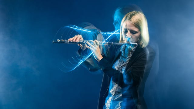 Photograph of a young woman playing a flute against a blue background. The slow exposure of the camera causes her movements to be traced across the image as a blur. She is surrounded by wisps of smoke.