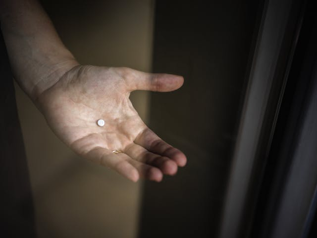 Photograph of a woman's hand holding an immunosuppressant prescription tablet, captured through a window.  The marking on the tablet looks like the letter G in lower case or the number 9.  There is a slight reflection in the window.