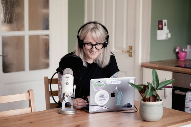 Photograph of a young woman with shoulder length blond hair seated indoors in a home environment at a kitchen table. She is wearing black glasses and a pair of large headphones over her ears. She has on a black t-shirt. She is smiling and looking down at the laptop which is resting on the tabletop in front of her. To her right is a professional looking microphone in a stand on the table. Her laptop is covered in stickers. Also on the table is a small house plant. In the background are the doors and countertop of the surrounding kitchen.