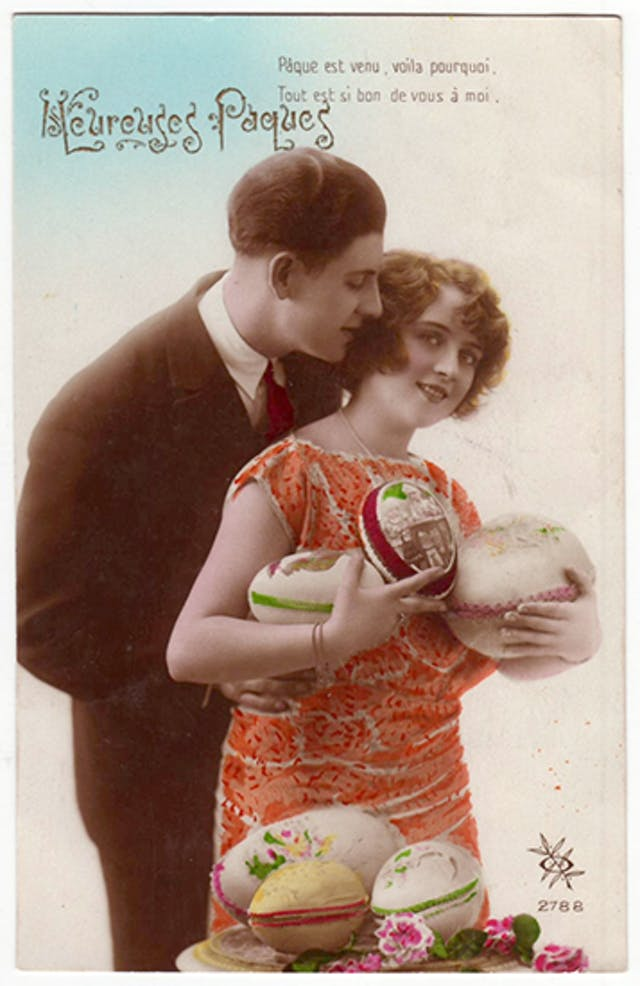 A young woman in an orage dress stands infront of an table with three large Easter eggs and scattered flowers on it, while she holds three large decorated easter eggs in her arms and a young man in a smart suit embraces her from behind,