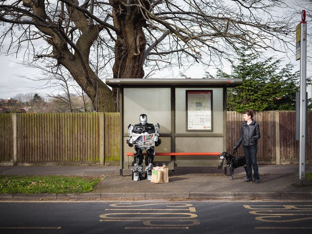 Photograph of a large robot sat at a bus stop reading the paper. At its feet are shopping bags. A woman with a dog is also waiting at the bus stop.
